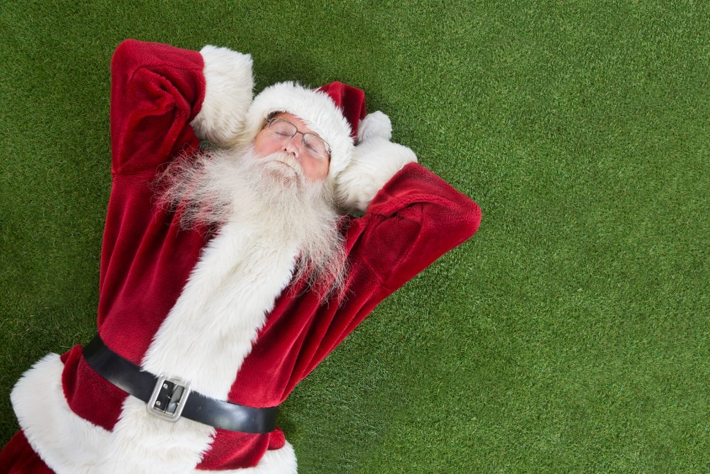 Santa lies, sleeps and has a nice dream on grass